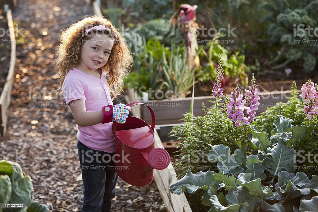 Little girl with watering can at community garden royalty-free stock photo