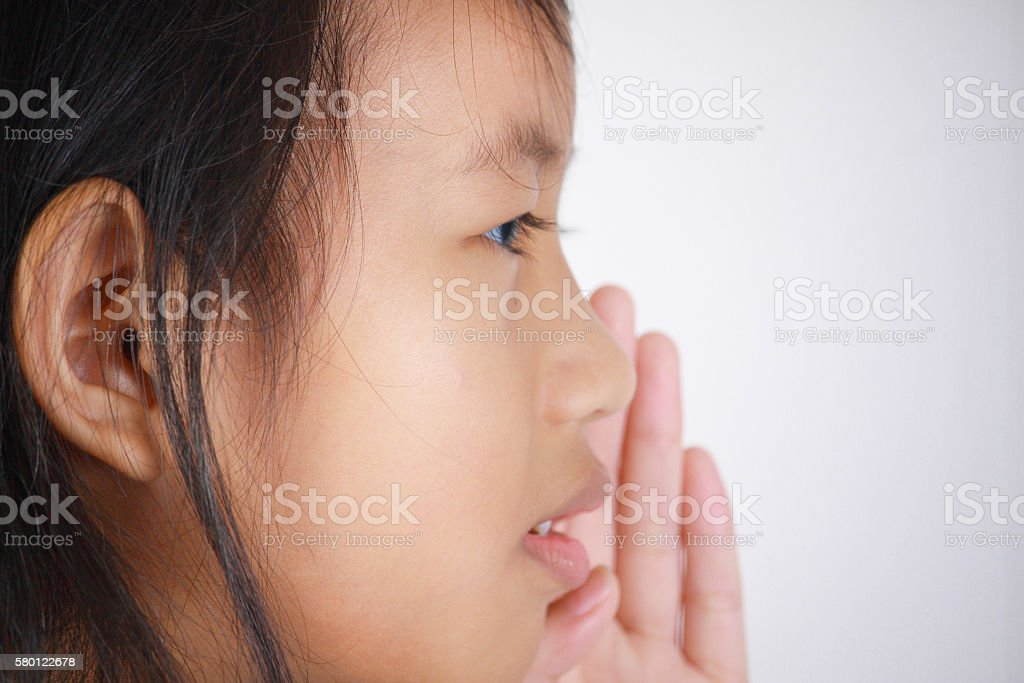 Little girl with whispering gesture stock photo