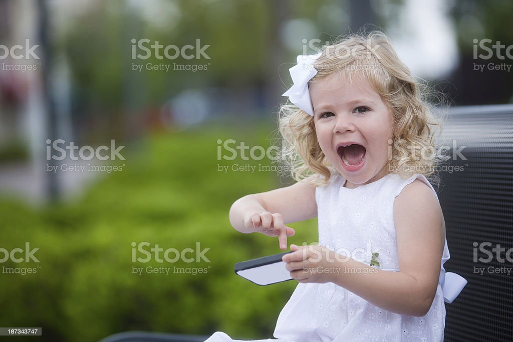 little girl with wild expression about her smart phone royalty-free stock photo