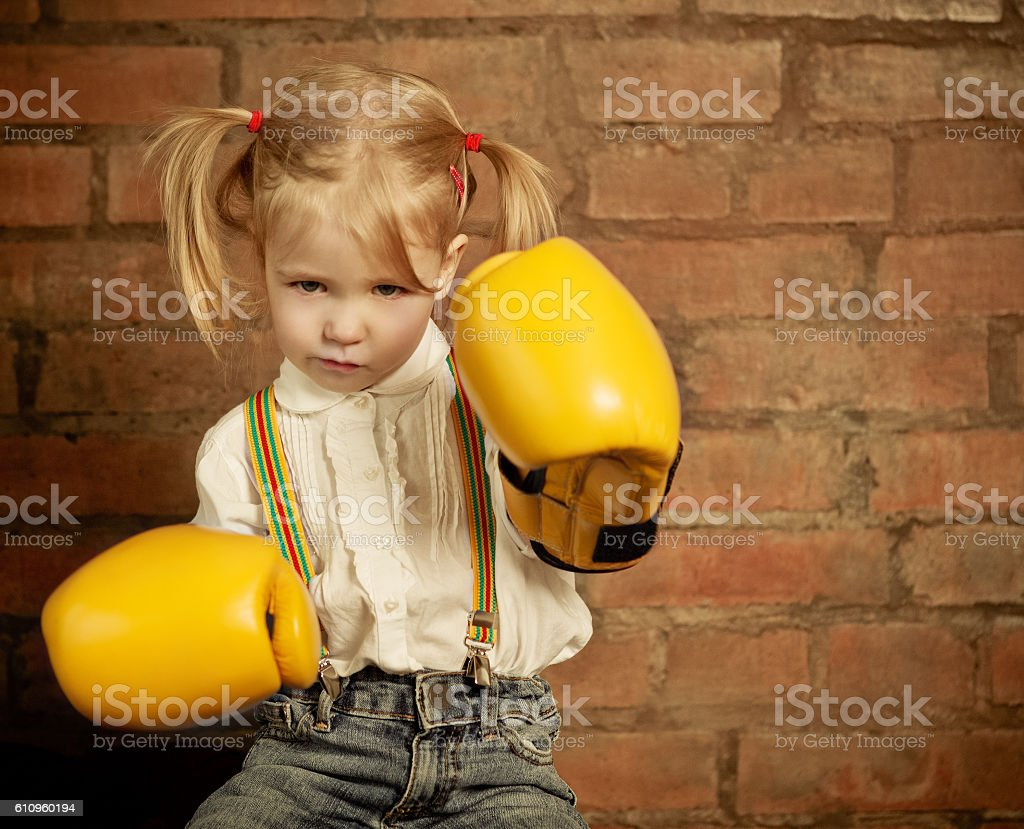 Little girl with yellow boxing gloves over brick wall stock photo