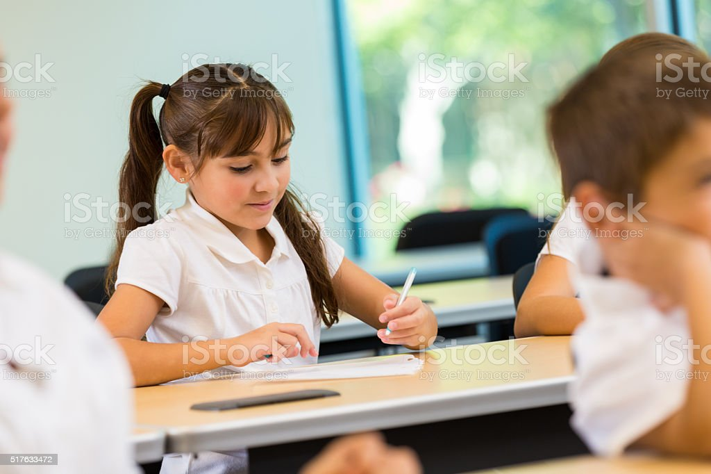 Private school elementary student works on assignment in class. She...
