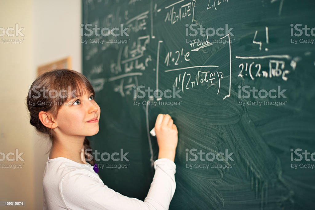 Little girl writing difficult mathematics equations stock photo