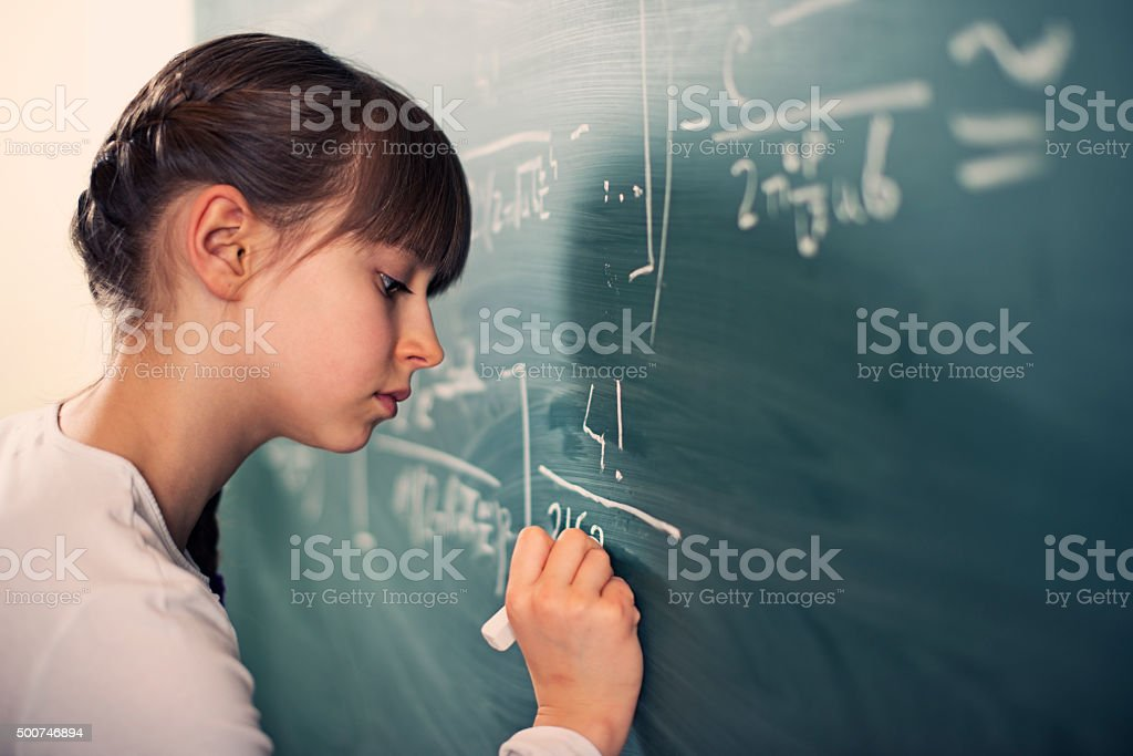 Little girl writing difficult mathematics equations stock photo
