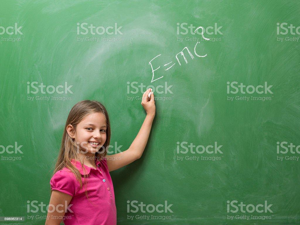 Little girl writing einstein's formula on blackboard stock photo