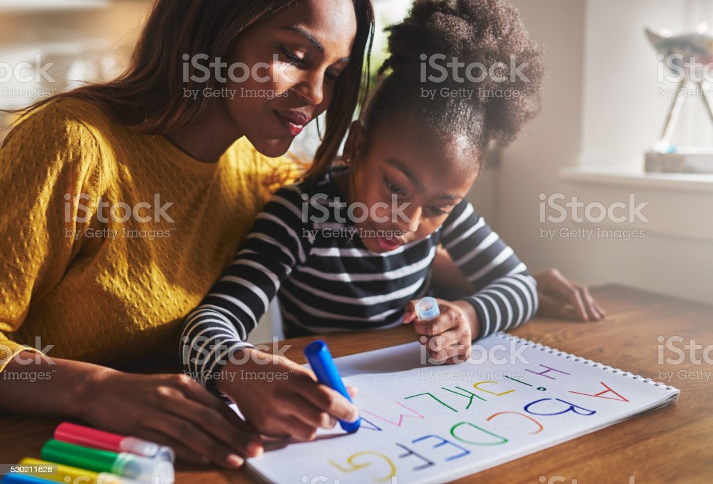 Little girl writing the alphabet stock photo