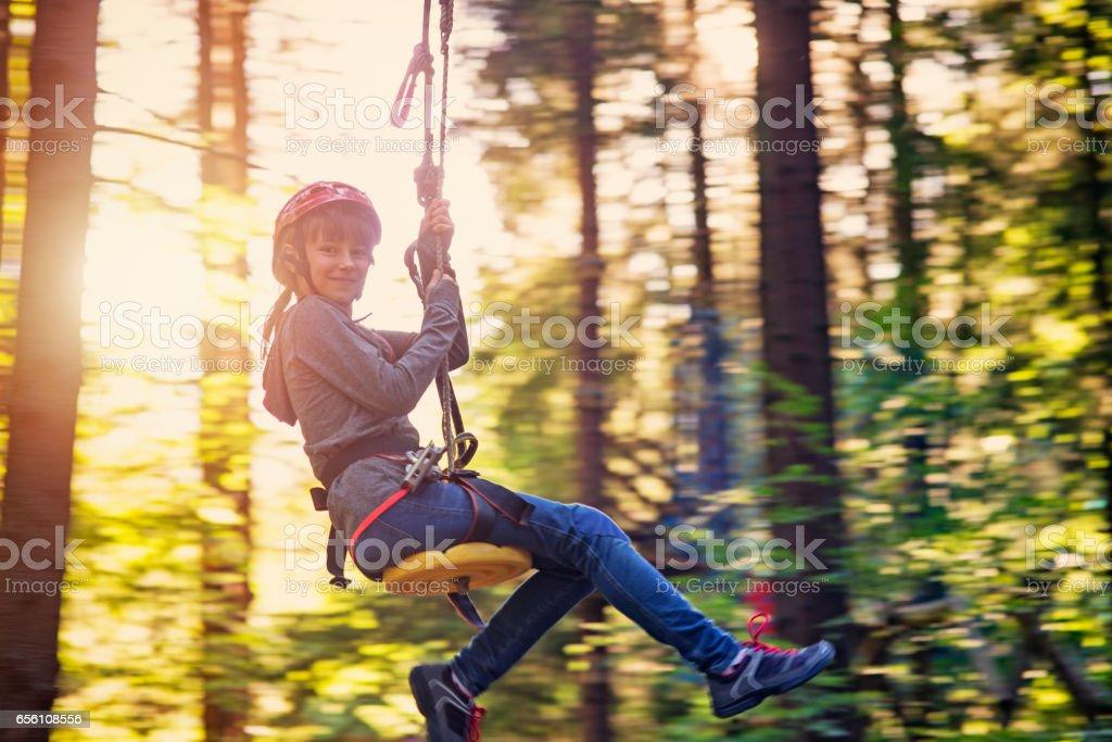 Little girl zip lining in adventure park stock photo