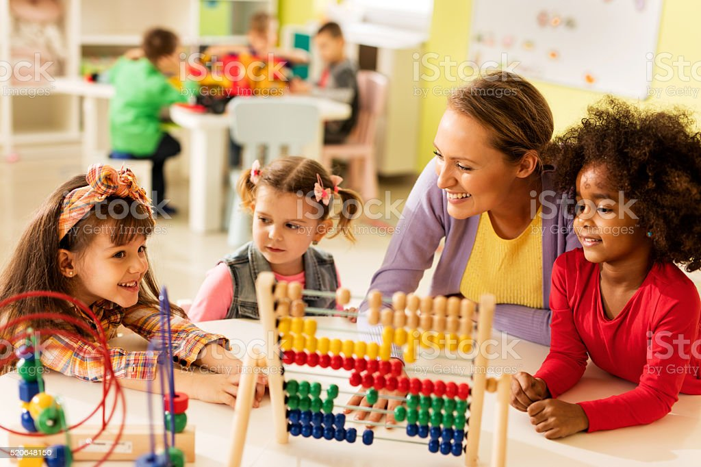 Little girls and teacher learning at preschool. stock photo