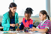 Little girls building robots during science class after school