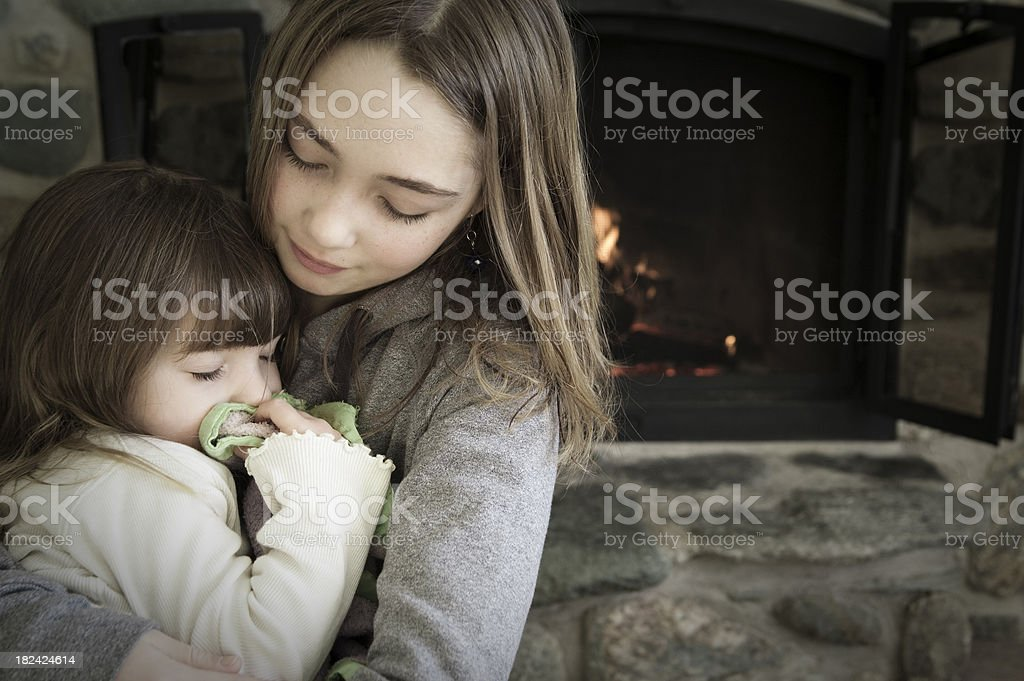 Little girls by the fireplace. stock photo