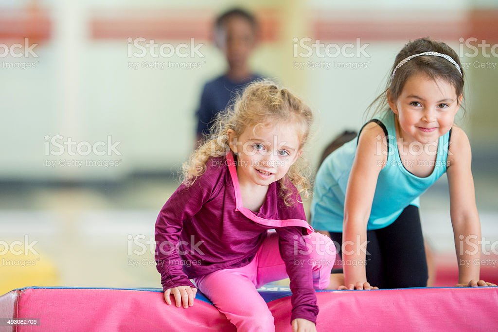 Little Girls Crawling Over Gym Mats stock photo