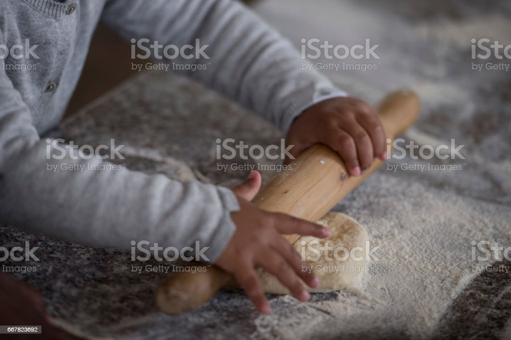 Little girl's hands making dough. stock photo