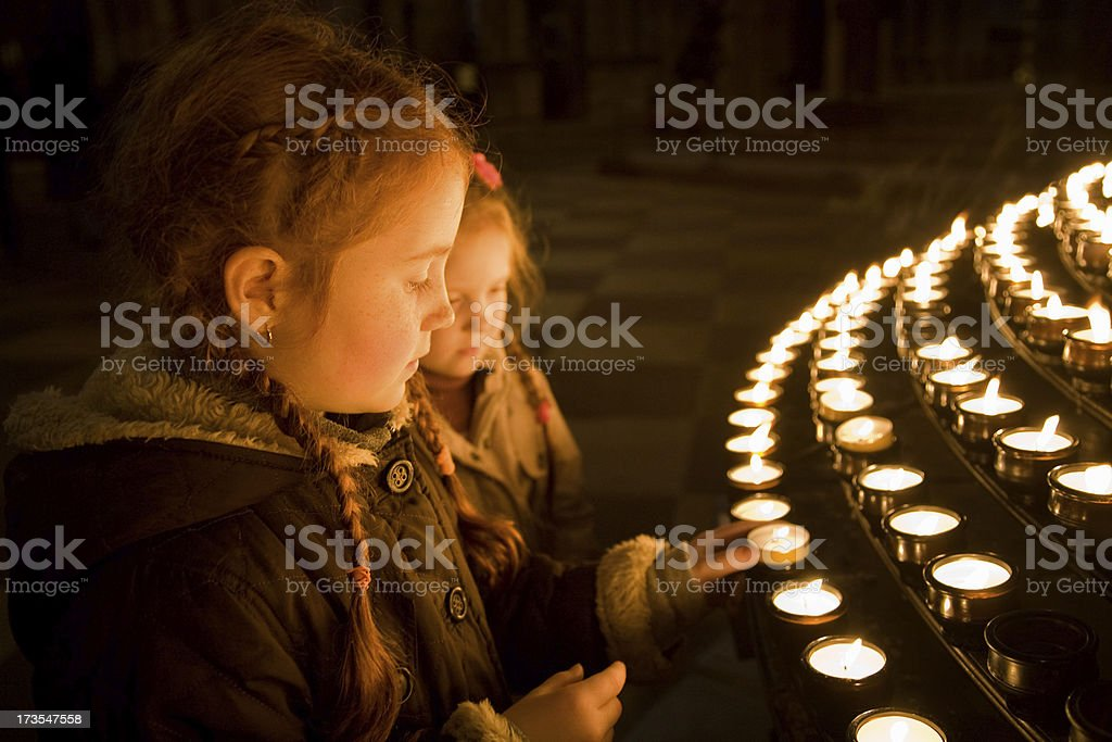 Little girls in church, lighting candles stock photo