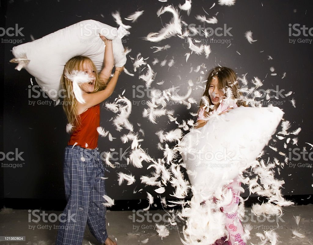 Little girls in pillow fight with feathers everywhere stock photo