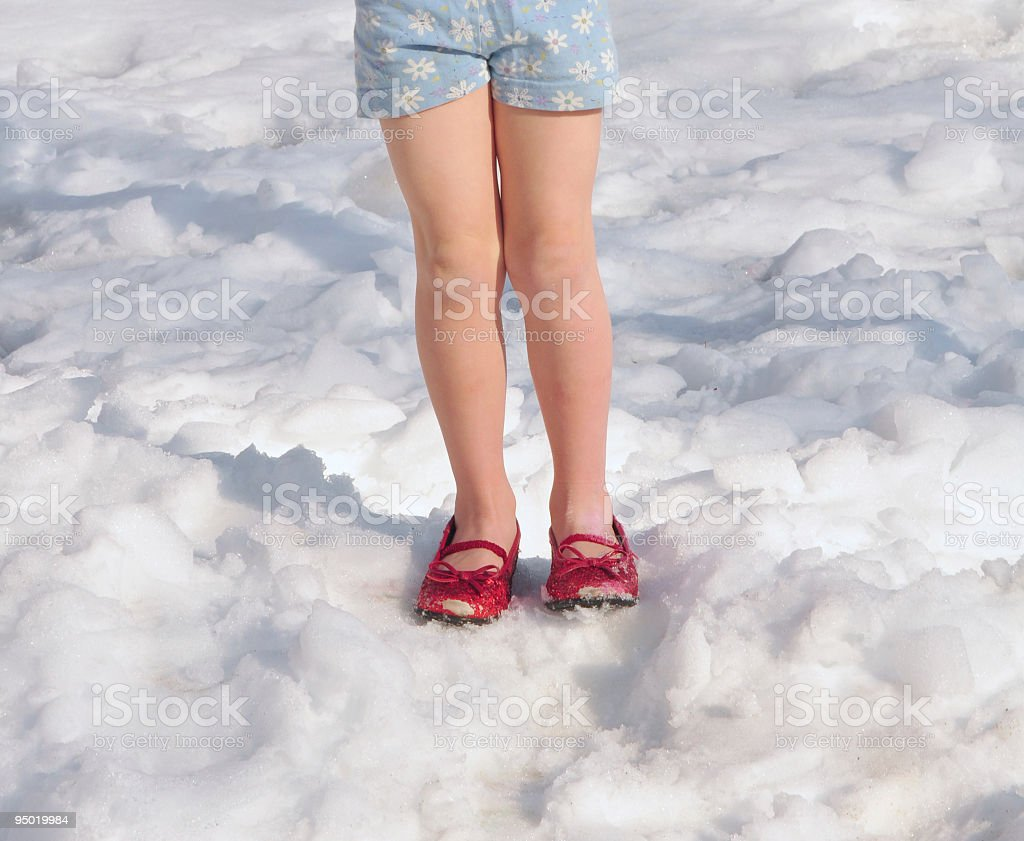 Little girl's legs in glitter shoes on snow royalty-free stock photo