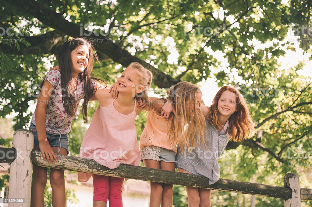 Little girls on fence under a tree on summer day stock photo