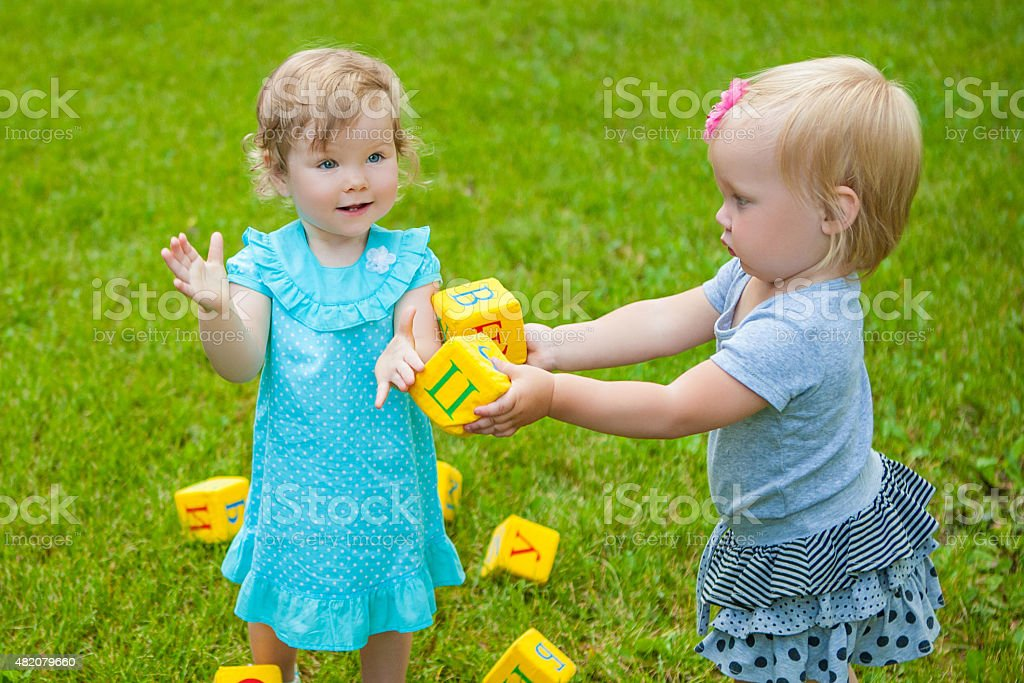 Little girls on nature playing toy stock photo