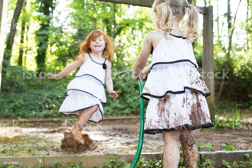 Little Girls Play in the Mud stock photo
