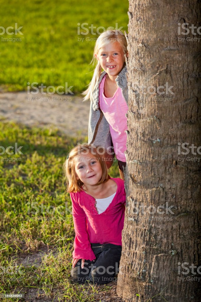 Little girls playing behind tree royalty-free stock photo