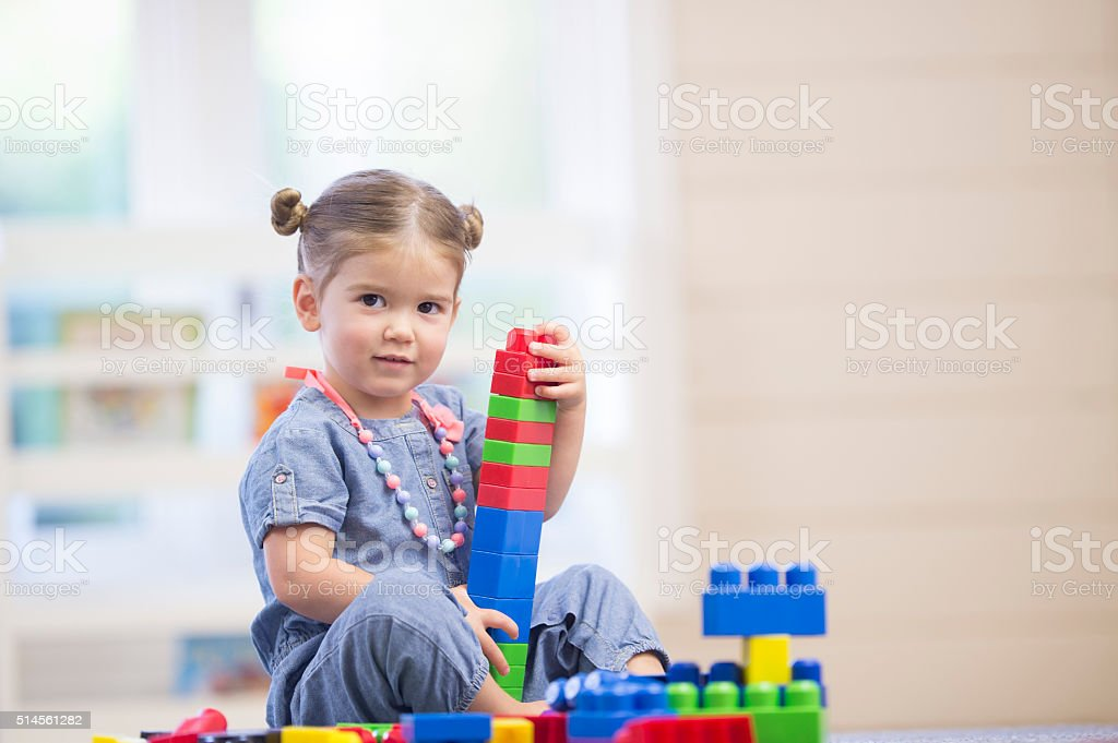 A cute little girl is playing with plastic blocks at daycare.