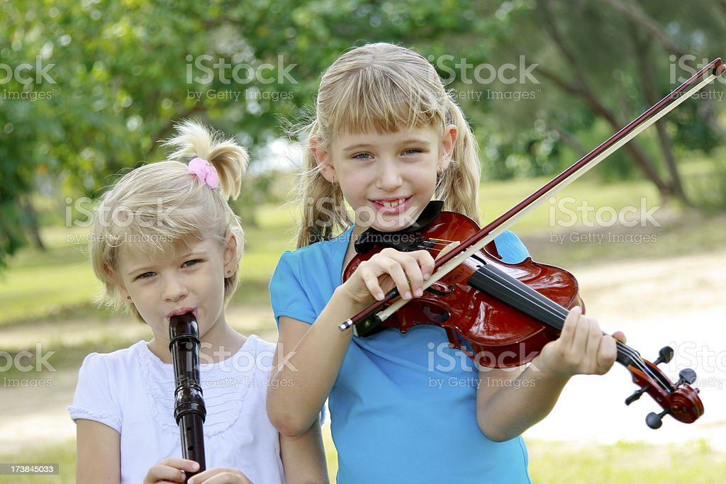 Little girls playing musical instruments royalty-free stock photo