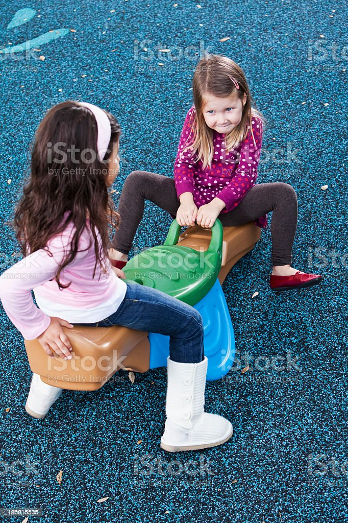 Little girls playing on seesaw stock photo