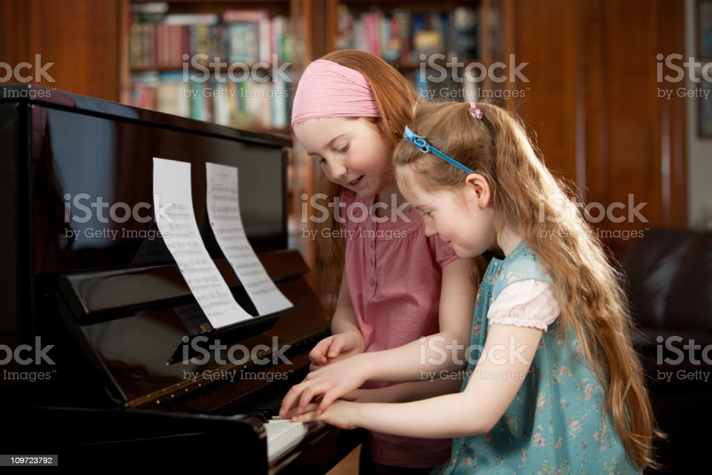 Little girls playing the piano royalty-free stock photo