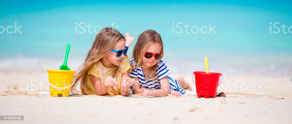 Little girls playing with beach toys during tropical vacation stock photo