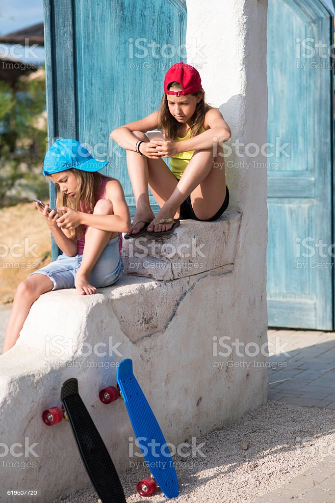 Little girls playing with smartphones stock photo
