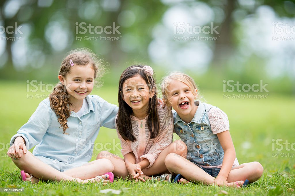 Little Girls Sitting in the Grass stock photo