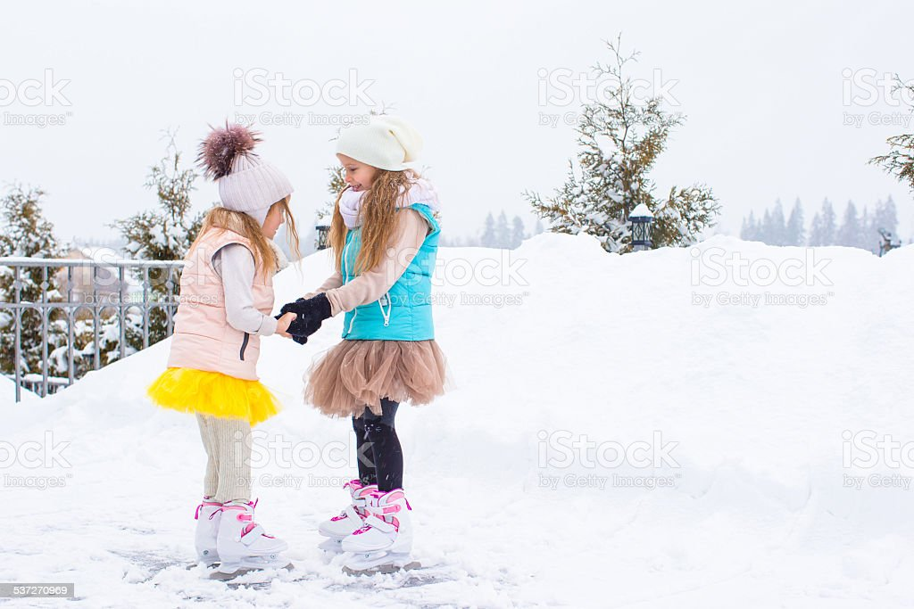 Little girls skating on ice rink outdoors in winter day stock photo