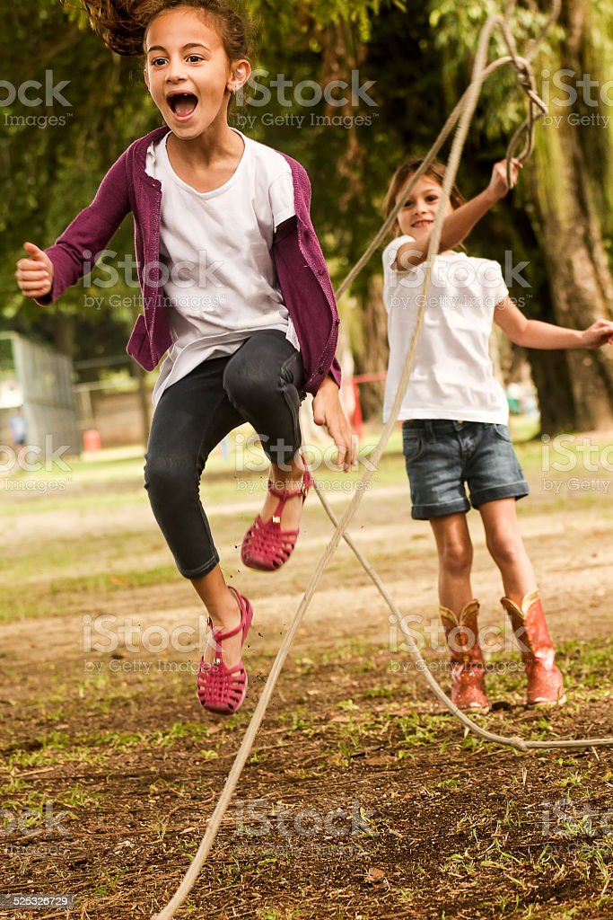 Little Girls Skipping Rope in Park stock photo