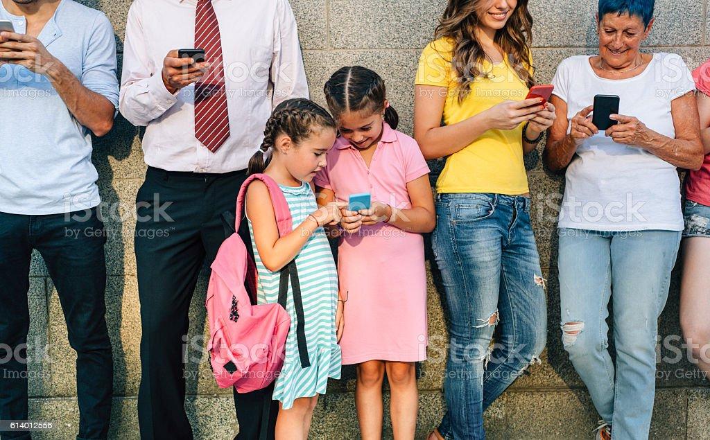 Little girls texting among adults stock photo