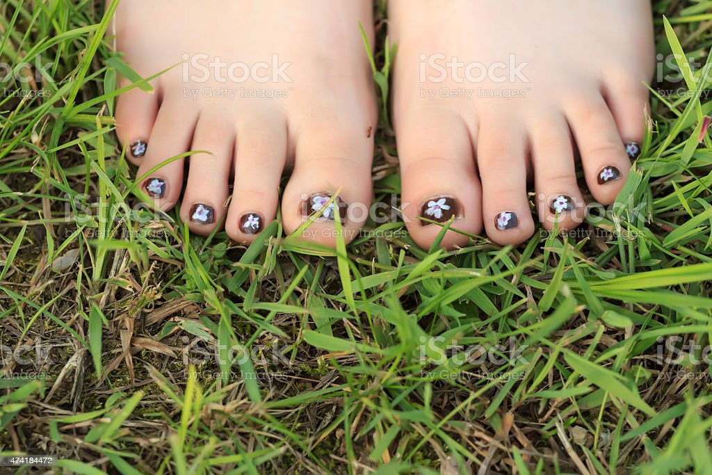 Little girl's toes with childish handmade nail art stock photo