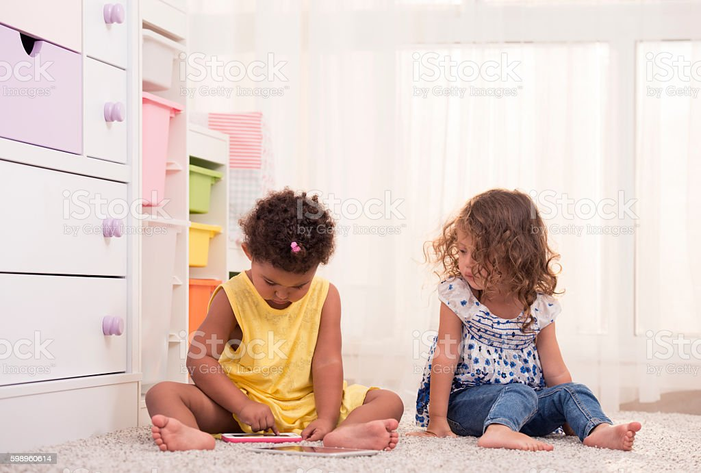 Little girls using smartphone. stock photo