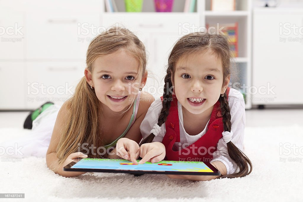 Little girls using tablet computer as artboard stock photo