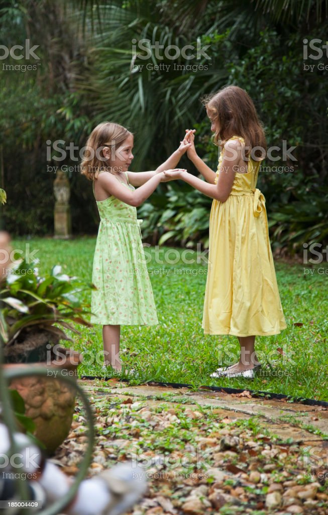 Little girls wearing sundresses playing in back yard stock photo