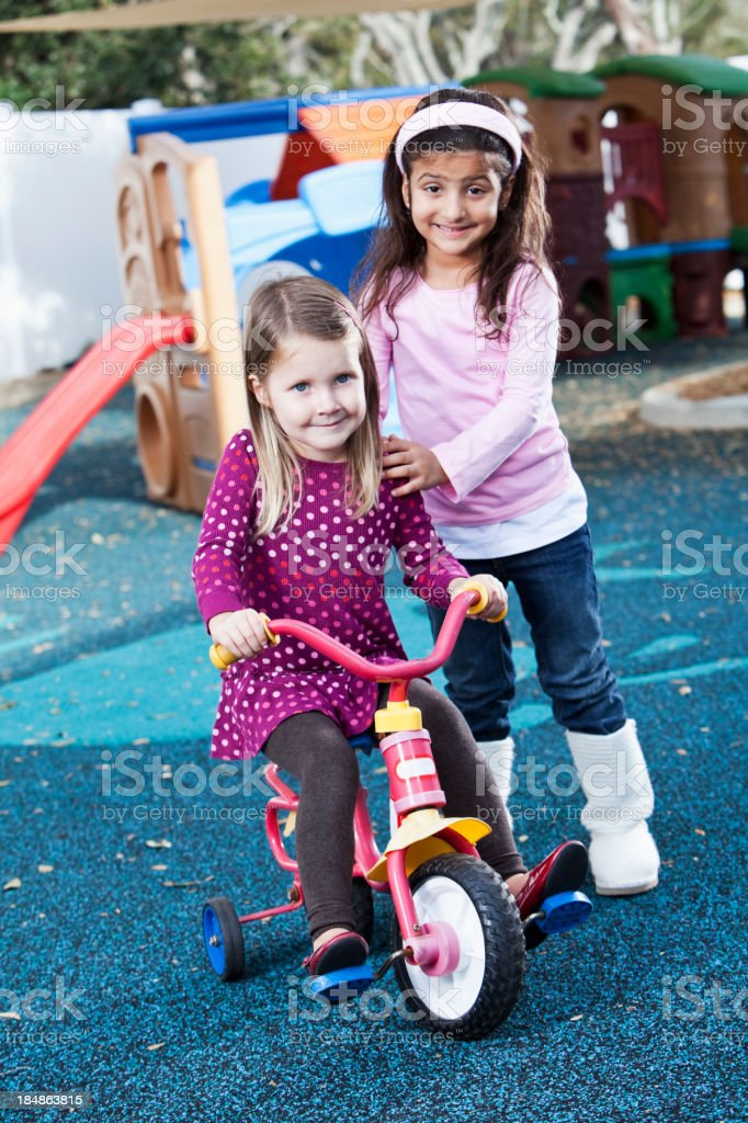 Little girls with bike on playground royalty-free stock photo