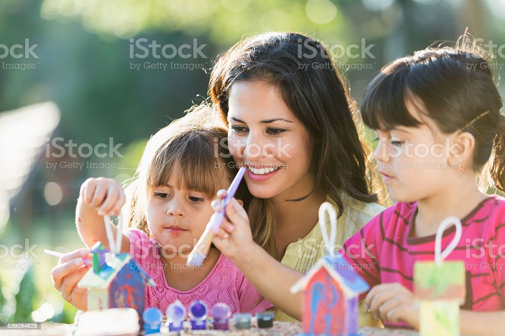 Little girls with mother painting bird houses stock photo