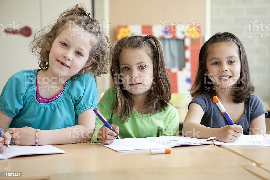 little girls writing in their classroom royalty-free stock photo