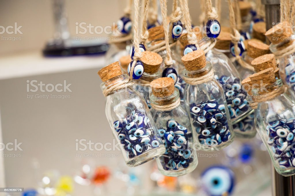 Little glass bottle filled with blue evil eye beads stock photo