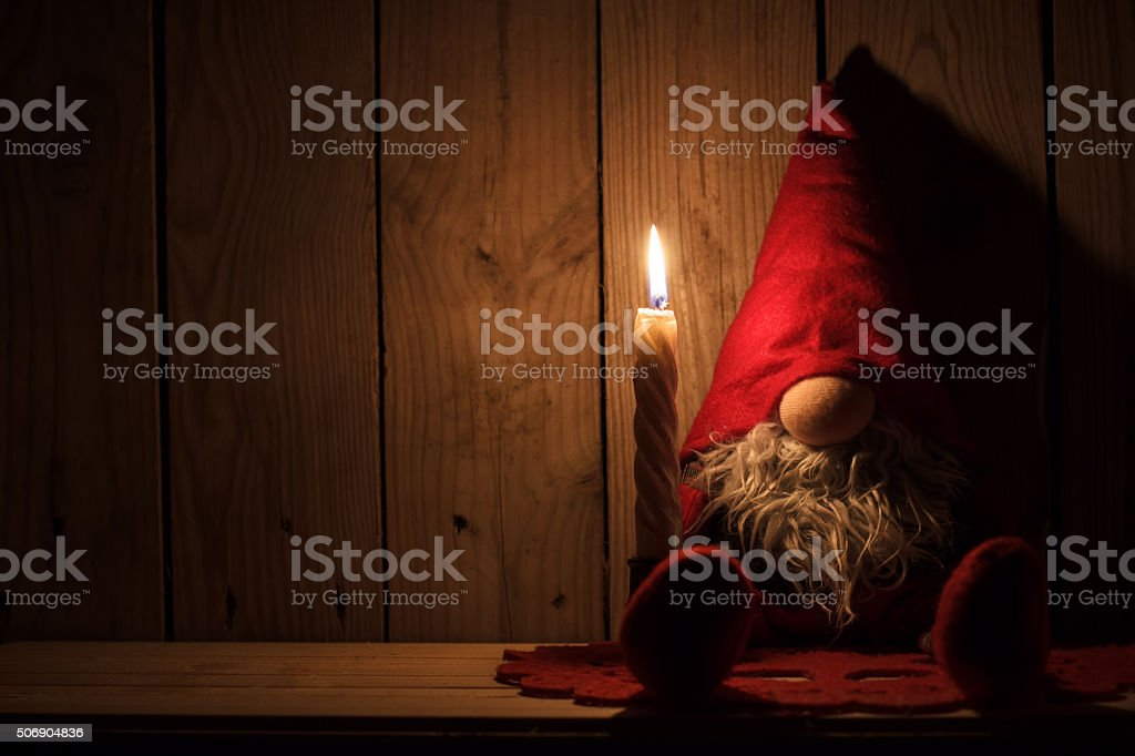 Little gnome sitting on wooden shelf with candle stock photo