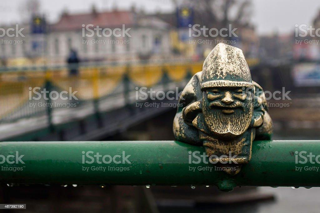 Little gnome statue on the bridge in the rain stock photo