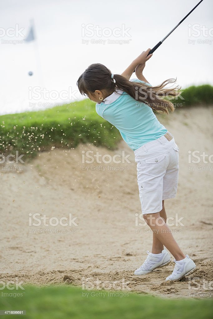 Little golfer hitting golf ball out of course sand trap stock photo