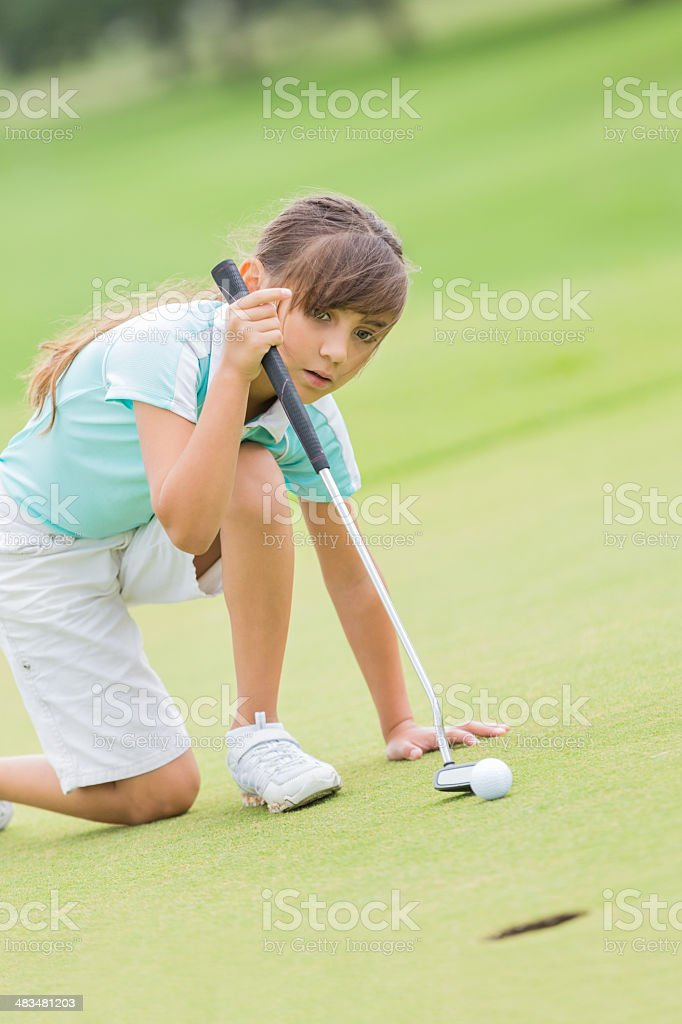 Little golfer lining up shot while playing on golf course royalty-free stock photo