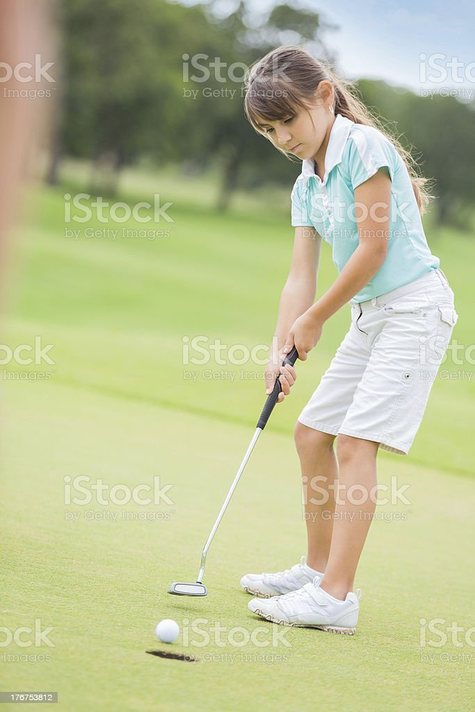 Little golfer putting on green during golf game stock photo