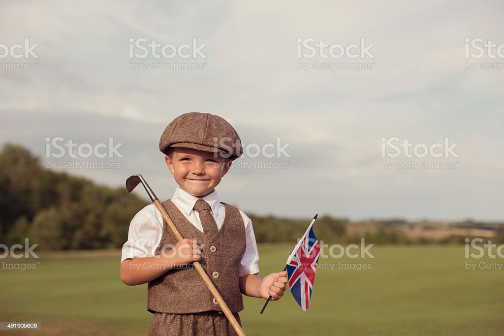 Little Golfing Boy in Vintage Attire Holding Union Jack stock photo