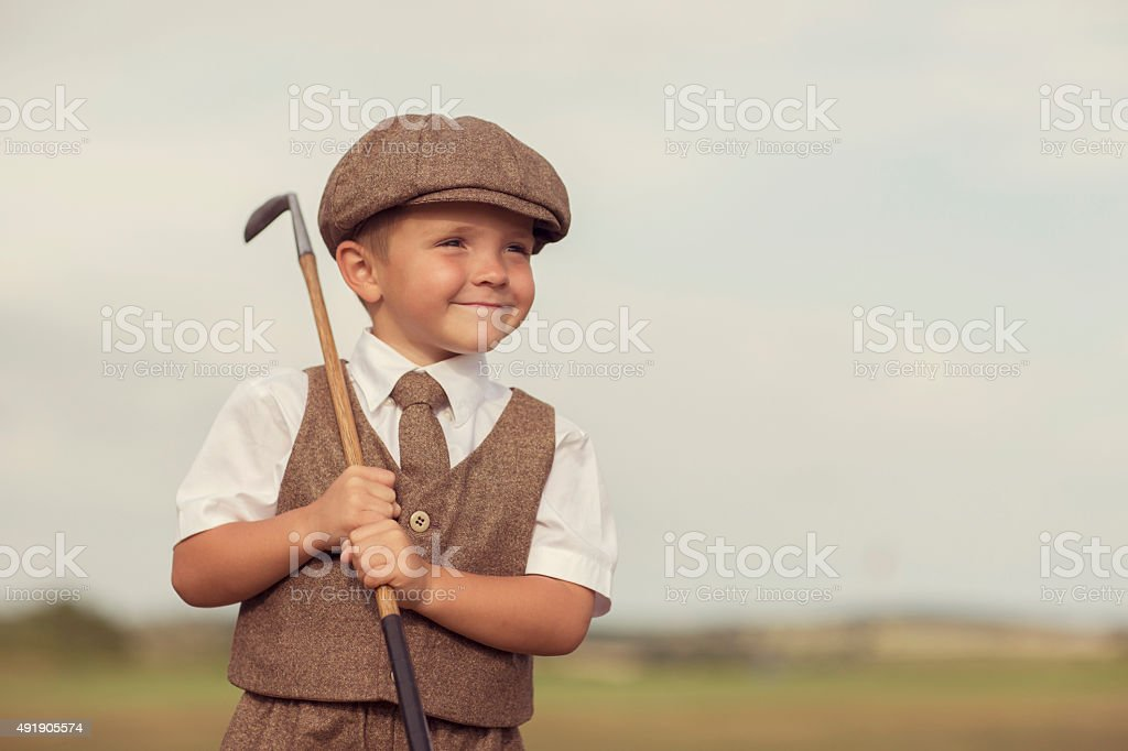 Little Golfing Boy in Vintage Attire stock photo