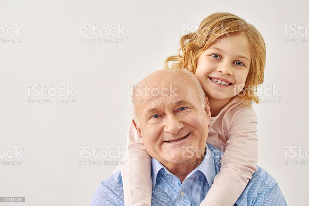 Little granddaughter hugging her grandfather stock photo