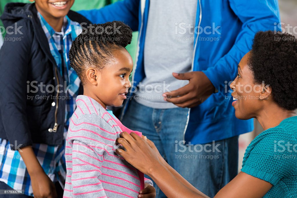 Little gril receives sweater at clothing drive stock photo