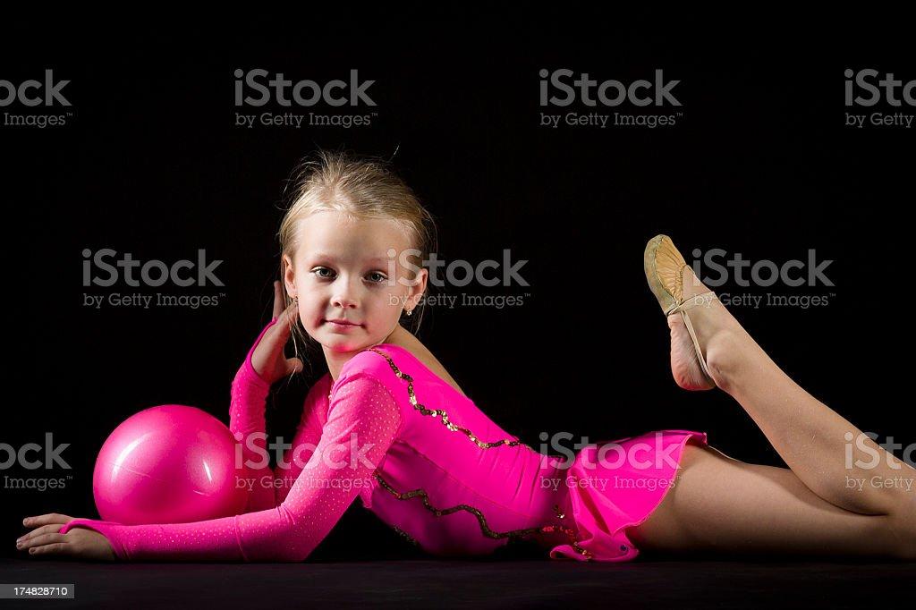 Little Gymnast girl with Rhythmic Ball on black background royalty-free stock photo